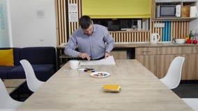 Lavoro d'ufficio di mattina I colleghi lavorano al t? della bevanda e della tavola, video d archivio