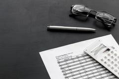 Lavoro del accounter di affari con il calcolo di imposte e vetri sul fondo nero della scrivania immagini stock libere da diritti
