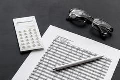 Lavoro del accounter di affari con il calcolo di imposte e vetri sul fondo nero della scrivania fotografie stock