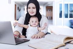 Lavoro del bambino e della madre con il computer portatile a casa Fotografia Stock Libera da Diritti