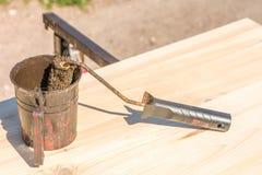 Lavoro del bordo di legno con la glassa di conservazione del legno con un rullo di pittura e un secchio della pittura immagine stock