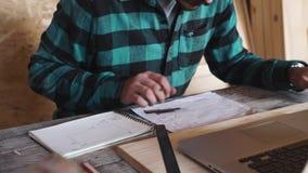 Lavoro del falegname nella sua officina con l'attrezzatura di disegno, la carta, il righello, la matita ed il computer portatile stock footage