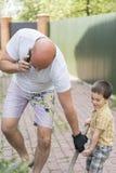 Lavoro del figlio e del papà nel giardino Il papà dice sul telefono ed il figlio tiene le molle Fotografie Stock Libere da Diritti