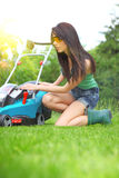 Lavoro del giardino, erba di falciatura della donna con la falciatrice immagini stock