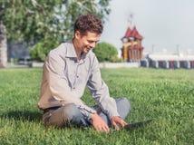 Lavoro del giovane con il computer portatile nel parco della città Fotografia Stock