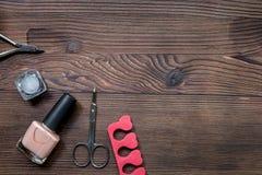 Lavoro del manicure con l'insieme di manicure e smalto per derisione di legno di vista superiore del fondo di cura delle mani su Immagini Stock