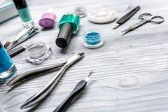 Lavoro del manicure con l'insieme di manicure e smalto per derisione grigia del fondo di cura delle mani su Fotografie Stock