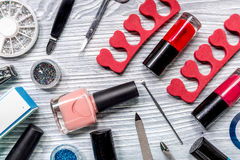 Lavoro del manicure con l'insieme di manicure e smalto per derisione grigia di vista superiore del fondo di cura delle mani su Fotografia Stock