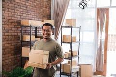 Lavoro del pacchetto della tenuta del corriere dell'uomo all'affare dell'imballaggio di spedizione fotografia stock
