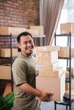 Lavoro del pacchetto della tenuta del corriere dell'uomo all'affare dell'imballaggio di spedizione immagini stock