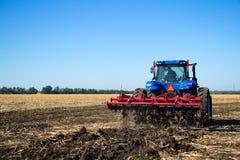Lavoro del trattore la terra su un'azienda agricola Immagini Stock Libere da Diritti