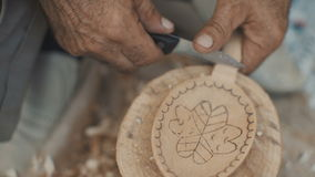 Lavoro del Woodcarver nel suo workshop Fabbricazione del cucchiaio di legno con il coltello stock footage