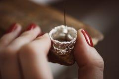 Lavoro delicato dei gioielli Chiuda su della mano di un gioielliere femminile che lavora ad un anello che ridimensiona al suo ban fotografie stock