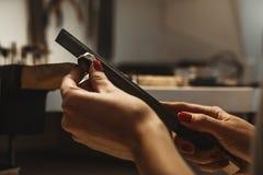 Lavoro delicato dei gioielli Chiuda su delle mani di un gioielliere femminile che funzionano e che modellano un anello non finito fotografia stock libera da diritti