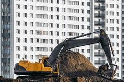 Lavoro dell'escavatore sulla terra su fondo di multi case del piano Fotografie Stock