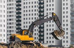 Lavoro dell'escavatore sulla terra su fondo di multi case del piano Fotografia Stock