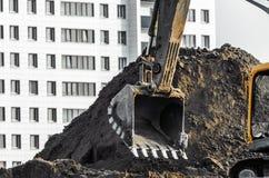 Lavoro dell'escavatore sulla terra su fondo di multi case del piano Fotografie Stock Libere da Diritti