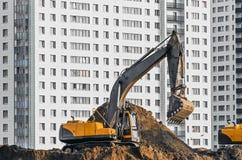 Lavoro dell'escavatore sulla terra su fondo di multi case del piano Immagine Stock