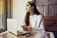 Lavoro della donna in caffè con il computer portatile vicino alla finestra con il latte del caffè Immagini Stock Libere da Diritti