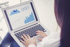 Lavoro della donna di affari del primo piano con analisi di finanza e dati di piallatura sul computer portatile fotografie stock