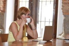 Lavoro della donna occupato alla caffetteria con il computer portatile che parla sul telefono cellulare Fotografie Stock