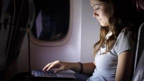 Lavoro della donna sul taccuino in aereo di linea, salone piano scuro durante vicino il volo video d archivio