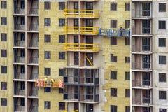 Lavoro della facciata ed isolamento di una costruzione a più piani immagine stock libera da diritti