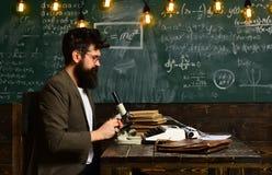 Lavoro dello scienziato con il microscopio Uomo con la barba e baffi a scuola L'uomo barbuto fa la ricerca sulla lavagna Fotografie Stock