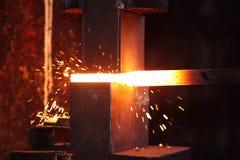 Lavoro dello Smith con il bastone dell'acciaio e del hammet Immagine Stock