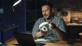 Lavoro di finitura dell'uomo attraente in ufficio che spegne computer portatile e lampada alla notte video d archivio
