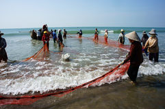 Lavoro di gruppo del pescatore sulla spiaggia Immagini Stock Libere da Diritti