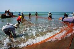 Lavoro di gruppo del pescatore sulla spiaggia fotografia stock