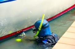 Lavoro di manutenzione del guscio della barca di pulizia dell'operatore subacqueo al bacino fotografia stock