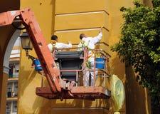 Lavoro di manutenzione della pittura di un monumento su una piattaforma mobile, Siviglia Spagna fotografia stock