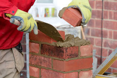 Lavoro di muratura - porre un mattone fotografia stock