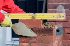 Lavoro di muratura - porre un mattone fotografie stock