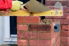 Lavoro di muratura - porre un mattone e controllarlo sono livello fotografia stock