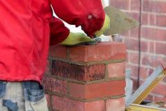Lavoro di muratura - porre un mattone sulla posta del portone fotografia stock libera da diritti