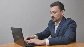 Lavoro di rivestimenti dell'uomo d'affari sul computer portatile stock footage
