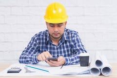 Lavoro di seduta dell'architetto o dell'ingegnere al suo scrittorio nell'ufficio Fotografie Stock Libere da Diritti
