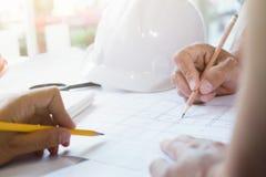 Lavoro di squadra dell'ingegnere che schizza un programma di costruzione di alloggi Immagini Stock