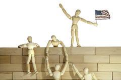 Lavoro di squadra o immigrati clandestini che scala una parete del confine di U.S.A. Fotografia Stock Libera da Diritti