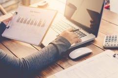 Lavoro di ufficio della tenuta dell'uomo d'affari sulla tavola e sull'analizzare il grafico di investimento che lavora nell'uffic fotografia stock