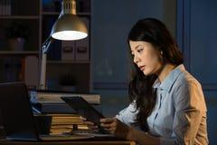 Lavoro digitale della compressa di affari di uso asiatico della donna recente fuori orario immagini stock