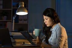 Lavoro digitale della compressa di affari di uso asiatico della donna recente fuori orario fotografie stock libere da diritti