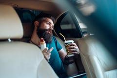 Lavoro a distanza Tempo del caffè alimenti a rapida preparazione - hot dog Pantaloni a vita bassa maturi con la barba Cura maschi fotografia stock libera da diritti