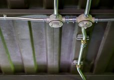 Lavoro elettrico del condotto sui tetti della lamina di metallo e delle travi di acciaio, porcile fotografie stock