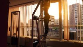 Lavoro esile della ragazza di sport della bionda duro in una palestra al tramonto in 4k stock footage