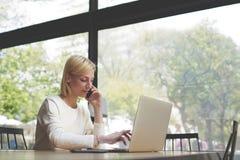 Lavoro femminile dello studente o delle free lance occupato sul NET-libro Immagine Stock