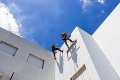 Lavoro industriale dell'alpinista sulla parete bianca Immagine Stock